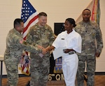 Defense Logistics Agency Aviation Army Maj. Alex Shimabukuro shakes the hand of Army Private Vennessa Baker, a native of Jamaica, during her naturalization ceremony May 30, 2017 at Fort Lee, Virginia's Soldier Support Center. Also pictured:  Army Lt. Col. Brian Neill, commander, 266th Quartermaster Battalion, center, and 266th Battalion Command Sergeant Major James Holmes, right.