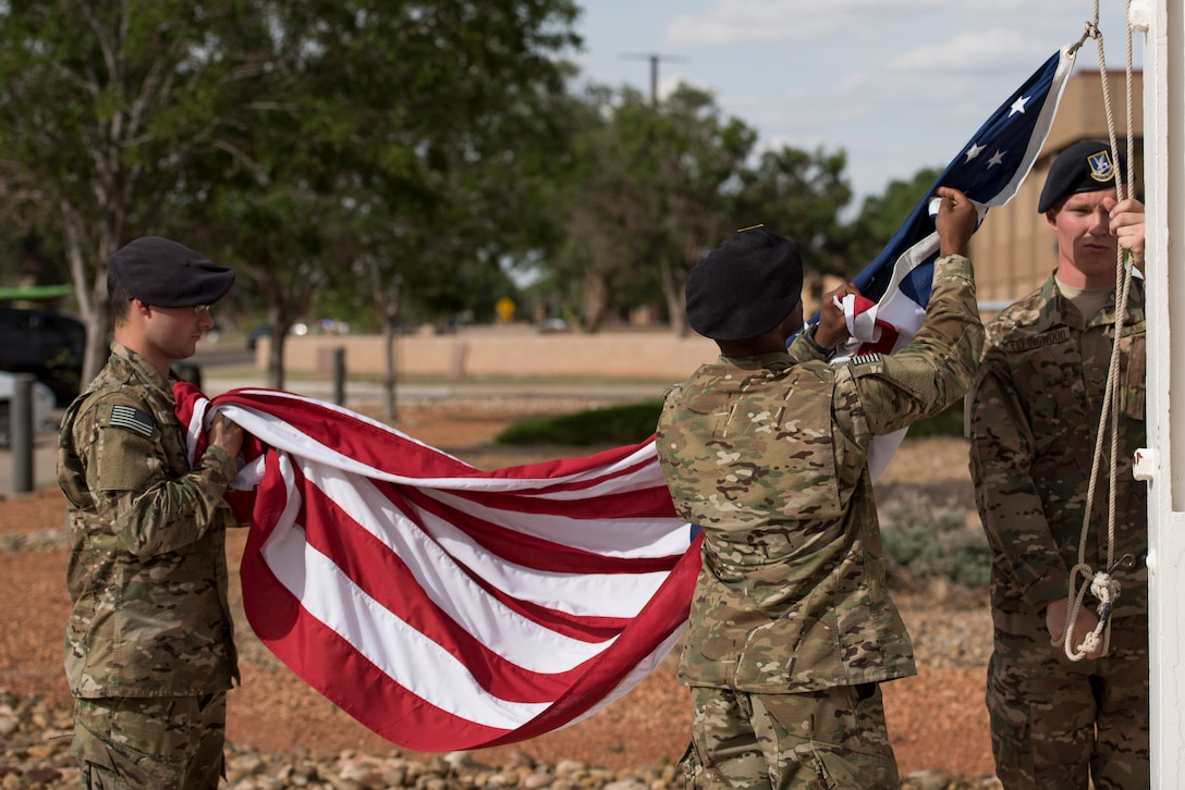 Members of the 27th Special Operations Security Forces Squadron lower the flag during retreat at the 524th Special Operations Squadron end of mission ceremony at Cannon Air Force Base, N.M., May 31, 2017. The 524th is relocating to Duke Field, Florida, where the command will change hands from the 27th SOW to the 492nd SOW. The 524th SOS has flown a wealth of aircraft throughout the years, including the B-18 Bolo, A-24 Banshee, P-47 Thunderbolt, F-82 Sabre, F-111 Aardvark, and the plane the squadron is currently flying: the C-146 Wolfhound. (U.S. Air Force photo by Staff Sgt. Michael Washburn/Released)