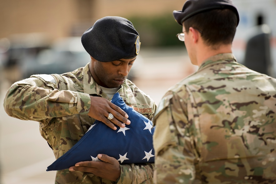 A member of the 27th Special Operations Security Forces Squadron folds an American flag during retreat at the 524th Special Operations Squadron end of mission ceremony at Cannon Air Force Base, N.M., May 31, 2017. The 524th is relocating to Duke Field, Florida, where the command will change hands from the 27th SOW to the 492nd SOW. The squadron has ties back to WWII, before it received its numerical designation of 524. (U.S. Air Force photo by Staff Sgt. Michael Washburn/Released)