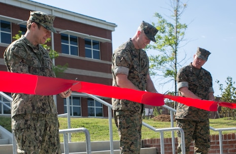 (From right to left) Lt. Gen. John E. Wissler, Commander, U.S. Marine Corps Forces Command, Col. John Evans, Commanding Officer, U.S. Marine Corps Security Force Regiment, and Navy Capt. Matthew Kosnar, Base Commander, Naval Weapons Station Yorktown, take part in a ribbon-cutting ceremony June 1, aboard Naval Weapons Station Yorktown, Va., for the official opening of the new Marine Corps Security Force Regiment Headquarters building. This was the beginning step to co-locating the three Fleet Anti-Terrorist Security Team companies that are currently scattered within the Hampton Roads area. (U.S. Marine Corps photo by Sgt. Kayla D. Rivera/Released)