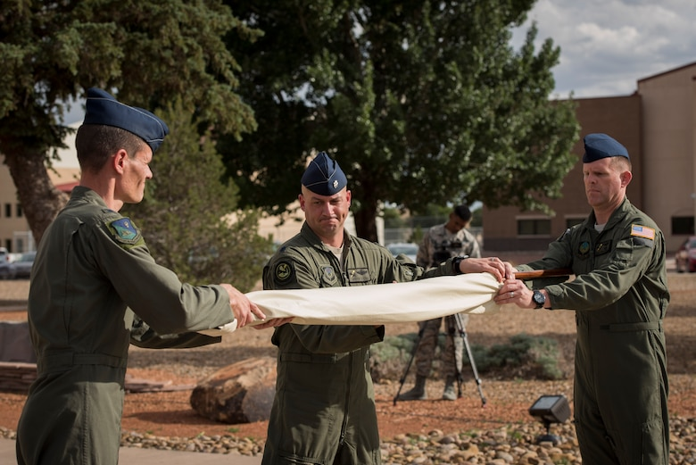 (Left) Col. Benjamin Maitre, 524th Special Operations Wing commander, (middle) Lt. Col. Derick Steed, 524th Special Operations Squadron commander, and Master Sgt. Chad Beach, 524 SOS first sergeant, ceremoniously cover the guidon during the 524 SOS end of mission ceremony at Cannon Air Force Base, N.M., May 31, 2017. The 524th is relocating to Duke Field, Florida, where the command will change hands from the 27th SOW to the 492nd SOW. The squadron has ties back to WWII, before it received its numerical designation of 524. (U.S. Air Force photo by Staff Sgt. Michael Washburn/Released)