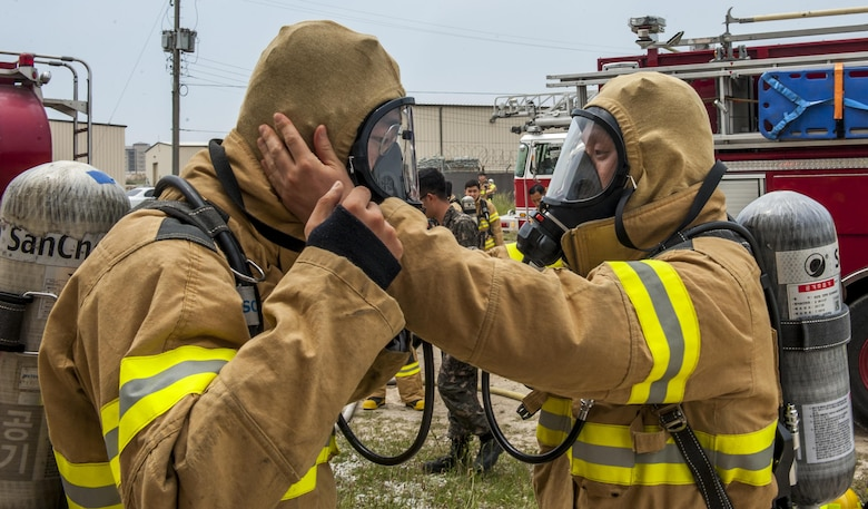 Republic of Korea Air Force firefighters perform buddy checks while donning personal protective gear during a combined fire training exercise at Kunsan Air Base, Republic of Korea, May 23, 2017. The firefighters conducted safety checks to ensure no skin was exposed during the live fire training portion of the exercise. (U.S. Air Force photo by Senior Airman Colville McFee/Released)