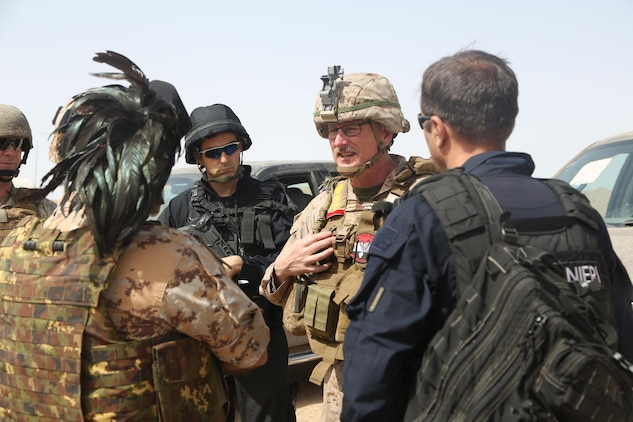U.S. Marine Corps Col. Christian Cabaniss, the commander of Task Force Al Taqaddum and deployed in support of Combined Joint Task Force – Operation Inherent Resolve, speaks with Italian police officials   about the current and future training plans for the Iraqi police and military forces on Al-Taqaddum Air Base, Iraq, April 27, 2017. Deploying U.S. Marines into the U.S. Central Command area of responsibility to conduct combined military training with our partner nations' security forces strengthens our vital relationships with partners in this strategically important region. This training is part of the overall CJTF-OIR building partner capacity mission by training and improving the capability of partnered forces fighting ISIS. CJTF-OIR is the global Coalition to defeat ISIS in Iraq and Syria.
