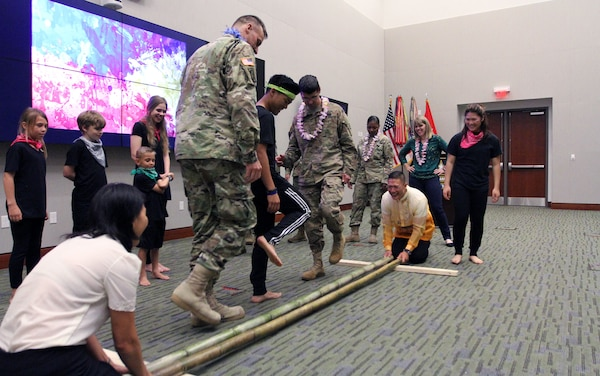 Several U.S. Army Central children teach the Tinikling to USARCENT members, as Col. Roy Banzon, USARCENT inspector general commander, and Marlyn Banzon, Banzon's wife, hit and tap the bamboo poles in rhythm to the music during USARCENT's observance for Asian American and Pacific Islander Heritage Month at Patton Hall May 24. (U.S. Army Photo by Sgt. Matthew Kuzara)