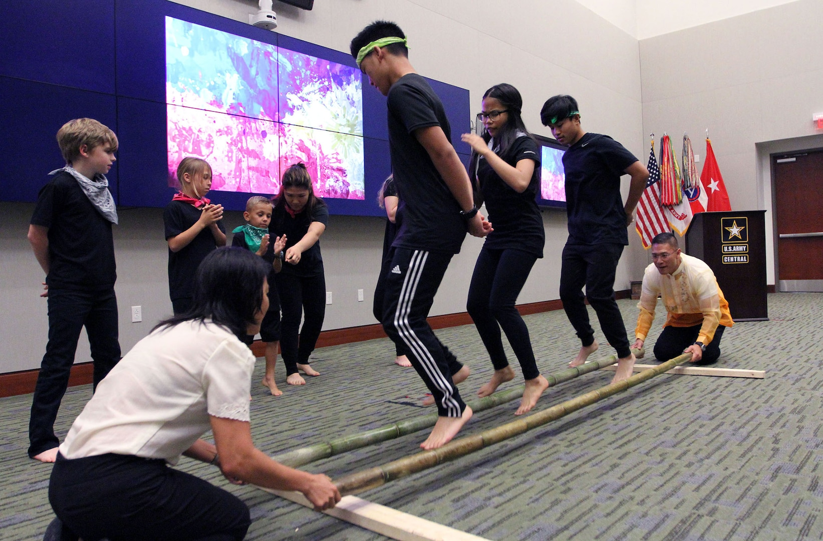 Several U.S. Army Central children perform the Tinikling, as Col. Roy Banzon, USARCENT inspector general commander, and Marlyn Banzon, Banzon's wife, hit and tap the bamboo poles in rhythm to the music during USARCENT's observance for Asian American and Pacific Islander Heritage Month at Patton Hall May 24. (U.S. Army Photo by Sgt. Matthew Kuzara)