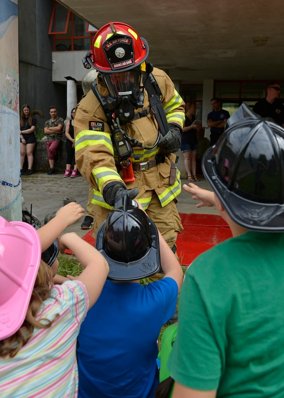 Tech. Sgt. Robert McClanahan, 31st Civil Engineer Squadron lead fire inspector, shakes hands with Italian children, May 31, 2017 at Polcinego, Italy. The children learned about the firefighter's suits, their equipment and what to do in case of a fire. (U.S. Air Force photo by Senior Airman Cary Smith)