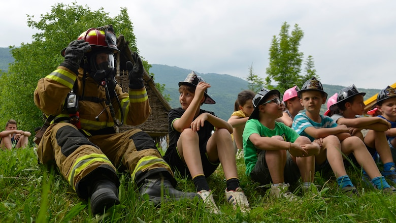 Tech. Sgt. Robert McClanahan, 31st Civil Engineer Squadron lead fire inspector, sits with students of an English after-school program during a fire safety demonstration, May 31, 2017 in Polcinego, Italy. The team brought a fire truck, Sparky the fire dog and several pieces of firefighting equipment. (U.S. Air Force photo by Senior Airman Cary Smith)