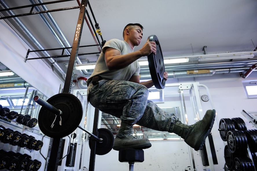 Airman 1st Class Nikko Madarang, 721st Aerial Port Squadron passenger service specialist, balances on one leg and squats during an exercise June 1, 2017, on Ramstein Air Base, Germany. June is Men's Health Month, and is used to heighten awareness of preventable health problems in men and boys, as well as encourage early treatment of disease. (U.S. Air Force photo by Airman 1st Class Savannah L. Waters)