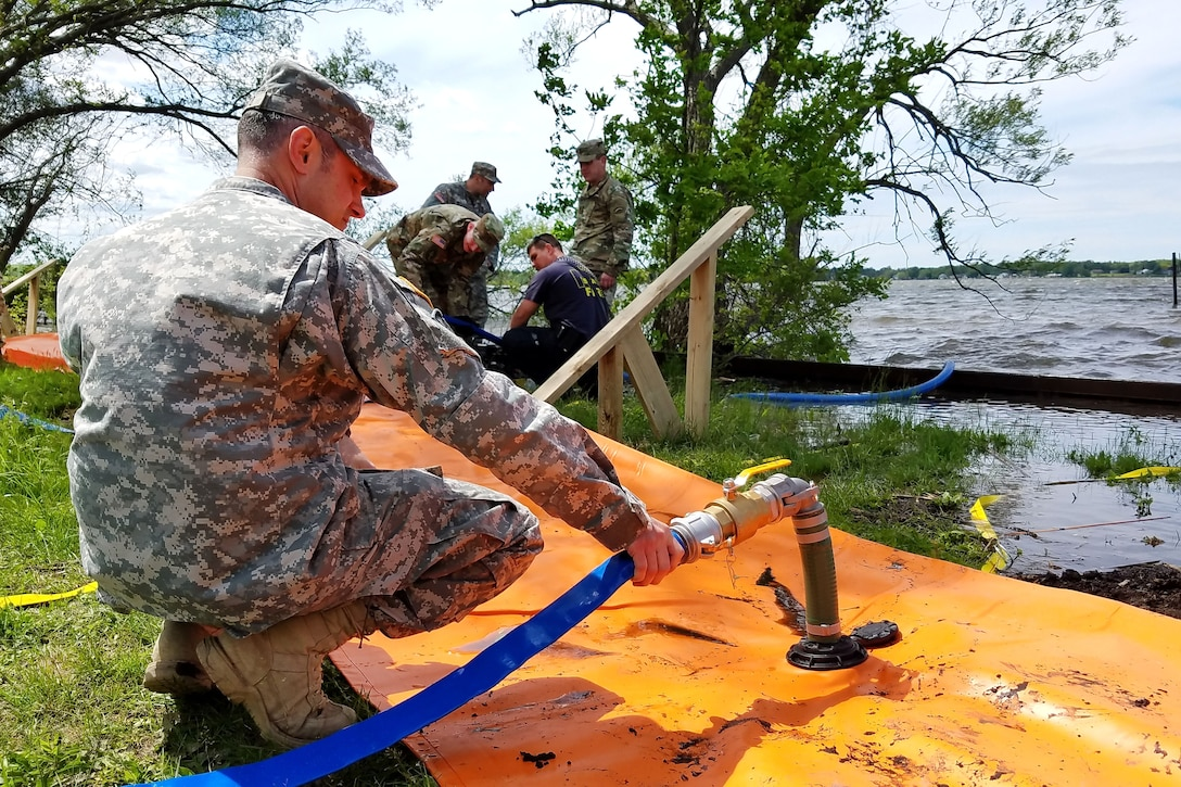 A guardsman adds water to the Tiger Dam flood control system .