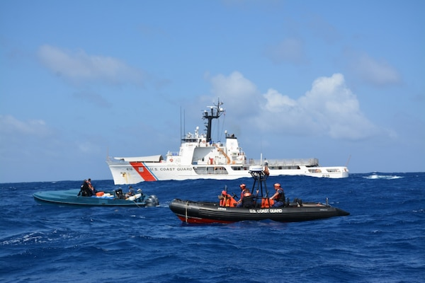 "A Coast Guard Cutter Diligence pursuit team interdicts a ""go-fast"" boat suspected of smuggling illegal drugs. From left to right in the in the ""go-fast"" is Lt. j.g. Edward Hobaica, and Petty Officer 2nd Class Jussen Gonzales, while from left to right on the Coast Guard response boat is Petty Officer 2nd Class Anthony Sanabria, Petty Officer 2nd Class Charles Murray and Petty Officer 1st Class Adam Mallard. (U.S. Coast Guard photo by Cutter Diligence/Released)"