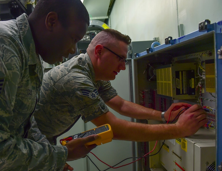 Staff Sgt. Dexter Calis, 460th Space Communications Squadron satellite communication supervisor and Senior Airman James Ramroth, 460th SCS SATCOM technician, perform multi-meter testing March 15, 2017, on Buckley Air Force Base, Colo. SATCOM ensures the flow data and connection between satellites and their end-users. (U.S. Air Force photo by Airman Jacob Deatherage/Released)