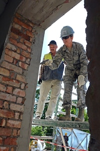 Senior Airman Samantha Ghareeb, a heavy equipment operator with the Kansas Air National Guard's 190th Civil Engineer Squadron, applies mortar to a building in Daugavpils, Latvia, in June 2015. Ghareeb was part of a humanitarian project between her unit and Latvian military engineers.