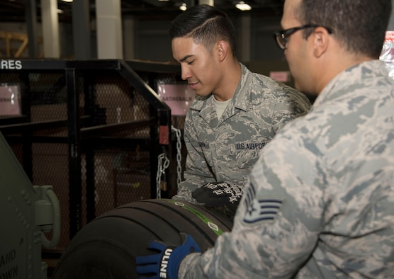 U.S. Air Force Senior Airman Jerod Garcia, left, an inventory technician and Staff Sgt. Bernardo Ostalaza, the NCO in charge of central storage, both assigned to the 6th Logistics Readiness Squadron, load a KC-135 Stratotanker aircraft wheel and tire onto a rack, June, 1, 2017 at MacDill Air Force Base, Fla. Supply Airmen help sustain aircraft parts that are required in the event an aircraft requires maintenance repairs. (U.S. Air Force photo by Airman 1st Class Adam R. Shanks)