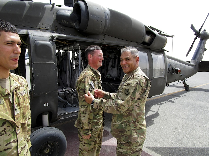 Lt. Gen. Michael Garrett, the commanding general of U.S. Army Central, presents Spc. Benjamin Baldwin, a UH-60 Blackhawk helicopter crew chief, for A Company, 2nd General Support Aviation Battalion, 149th Aviation Regiment, with his first combat patch, during an impromptu combat patch ceremony on the helicopter landing pad, on Ali Al Salem Air Base, May 20. Garrett surprised the crew chiefs with the impromptu stop and shared his story of how he received his first combat patch.  (U.S. Army photo by Lt. Col. Derek Johnson, USARCENT)