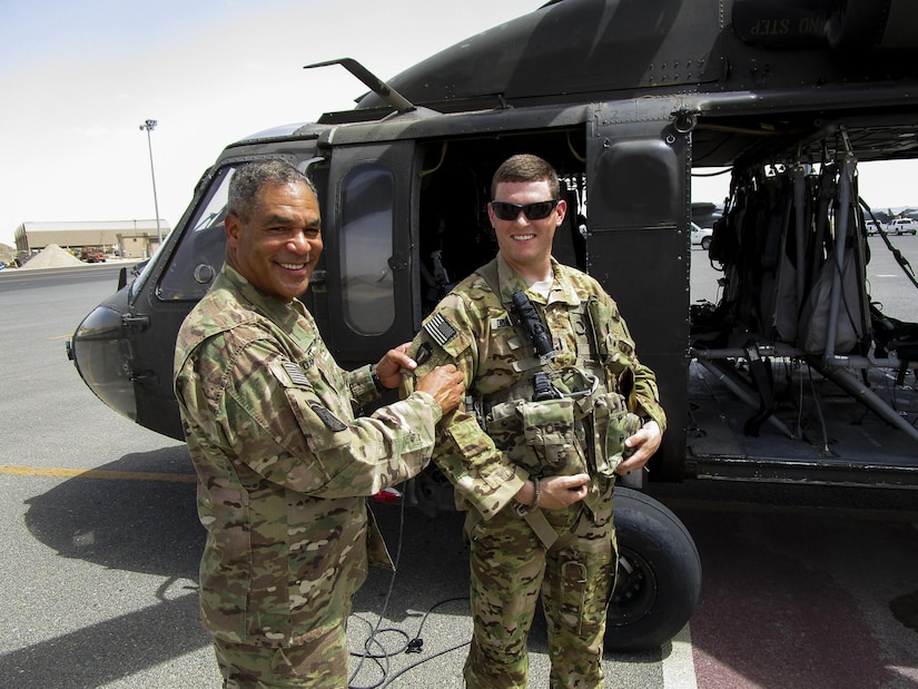 Lt. Gen. Michael Garrett, the commanding general of U.S. Army Central, presents 1st Lt. Benjamin Gonzalez, the platoon leader for A Company, 2nd General Support Aviation Battalion, 149th Aviation Regiment, with his combat patch during an impromptu combat patch ceremony on the helicopter landing pad, on Ali Al Salem Air Base, May 20. Gonzalez organized the surprise combat patch ceremony for the new crew chiefs.  (U.S. Army photo by Lt. Col. Derek Johnson, USARCENT)