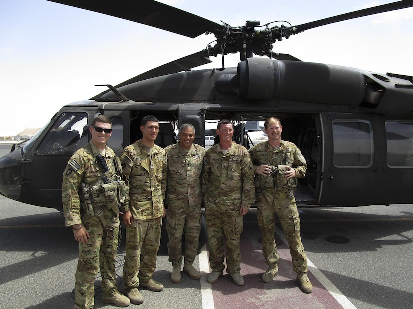 Lt. Gen. Michael Garrett, the commanding general of U.S. Army Central, stands with (left) 1st Lt. Benjamin Gonzales, (direct left of Garrett) Spc. Jesus Santiago, (direct right of Garrett) Spc. Benjamin Baldwin, and (right) Chief Warrant Officer 2 Richard Minton, a UH-60 Blackhawk helicopter crew, for A Company, 2nd General Support Aviation Battalion, 149th Aviation Regiment, after an impromptu combat patch ceremony on the helicopter landing pad at Ali Al Salem Air Base, May 20. Gonzalez organized the surprise combat patch ceremony for the new crew chiefs. (U.S. Army photo by Lt. Col. Derek Johnson, USARCENT)