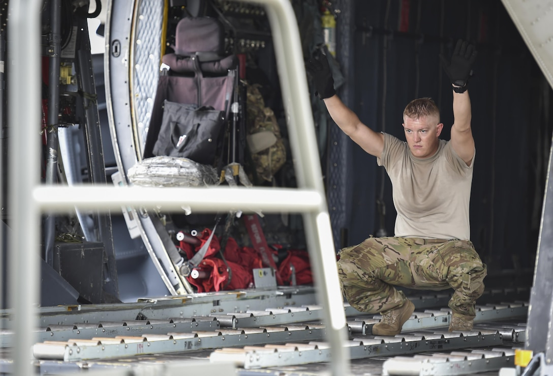 Staff Sgt. Josh Kindell, a loadmaster with the 15th Special Operations Squadron, guides a cargo loader onto an MC-130H Combat Talon II at Hurlburt Field, Fla., May 30, 2017. Loadmasters loaded the Combat Talon with cargo to drop in flight for a training mission to ensure their precision global reach capability. (U.S. Air Force photo by Airman 1st Class Joseph Pick)