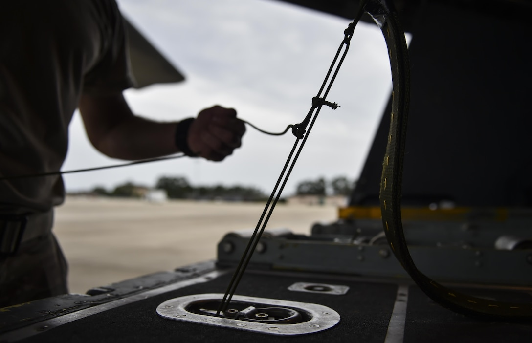 Tech. Sgt. Zach Kelhi, a loadmaster with the 15th Special Operations Squadron, ties down a heavy equipment extract parachute line to an MC-130H Combat Talon II at Hurlburt Field, Fla., May 30, 2017. After an extract parachute is deployed, the wind force pulls cargo off the ramp of aircraft. (U.S. Air Force photo by Airman 1st Class Joseph Pick)