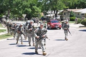 In a photo from 2011, officer candidates take a tactical march in a neighborhood in Rapid City, S.D.