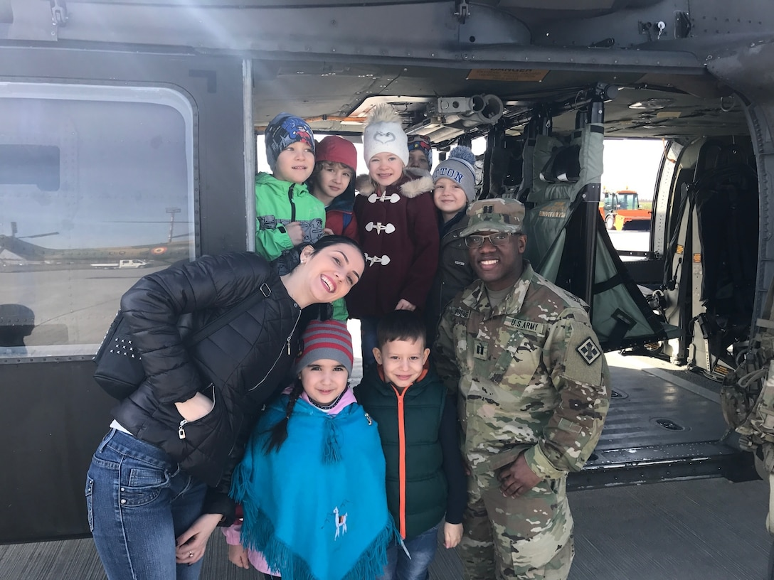 Capt. Jordan Rusher, a signal officer, 926th Engineer Brigade, poses with the local youth, May, 26, 2017. The event included static displays of military vehicles, including tanks, helicopters and Romanian jets. Cpt. Rusher's attendance advances the efforts of Resolute Castle 2017 in support of Operation Atlantic Resolve. Resolute Castle 17 is an exercise strengthening the NATO alliance and enhancing its capacity for joint training and response to threats within the region.