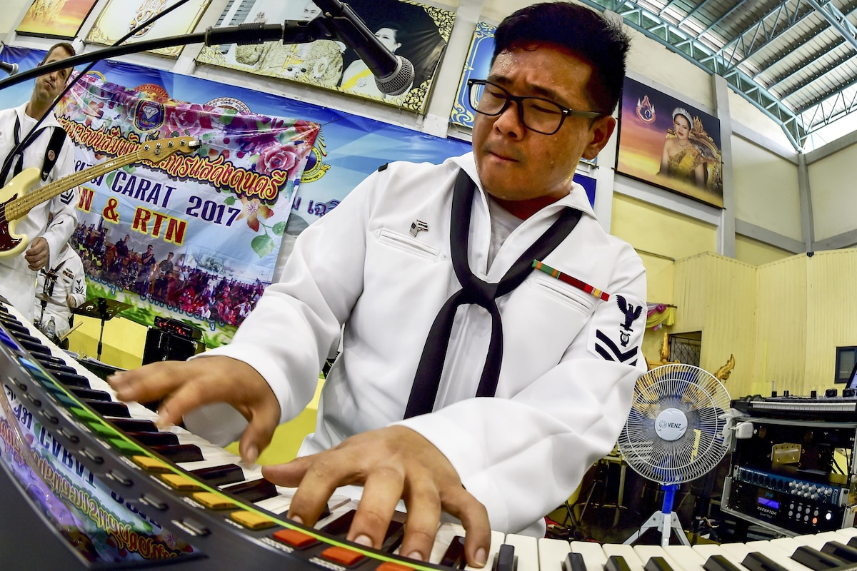A sailor jams on a keyboard at a band performance.