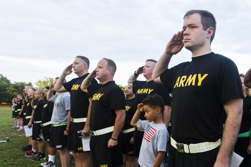 Miles Wiggins, the son of Maj. Ryan Wiggins, an operations officer at the U.S. Army Reserve Command, salutes the flag alongside Soldiers assigned to USARC before participating in an urban-orienteering event, at Fort Bragg, N.C., June 2, 2017. The event was designed to promote individual and unit readiness by ensuring everybody stays physically fit, enhance team cohesion and improve spirit de corps. Orienteering is a competitive form of land navigation. It combines map reading, terrain study, strategy, competition and exercise. (U.S. Army Reserve photo by Sgt. Stephanie Ramirez)