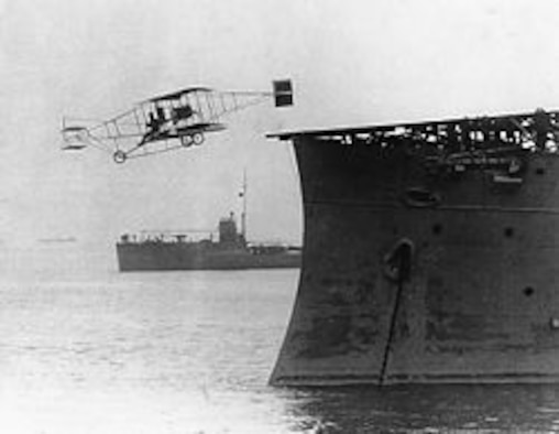 Eugene B. Ely takes off in a Curtis pusher aircraft from a platform built over the bow of the USS Birmingham, Nov. 14, 1910, Hampton Roads, Virginia. Ely demonstrated the concept that became the aircraft carrier. (Courtesy photo)