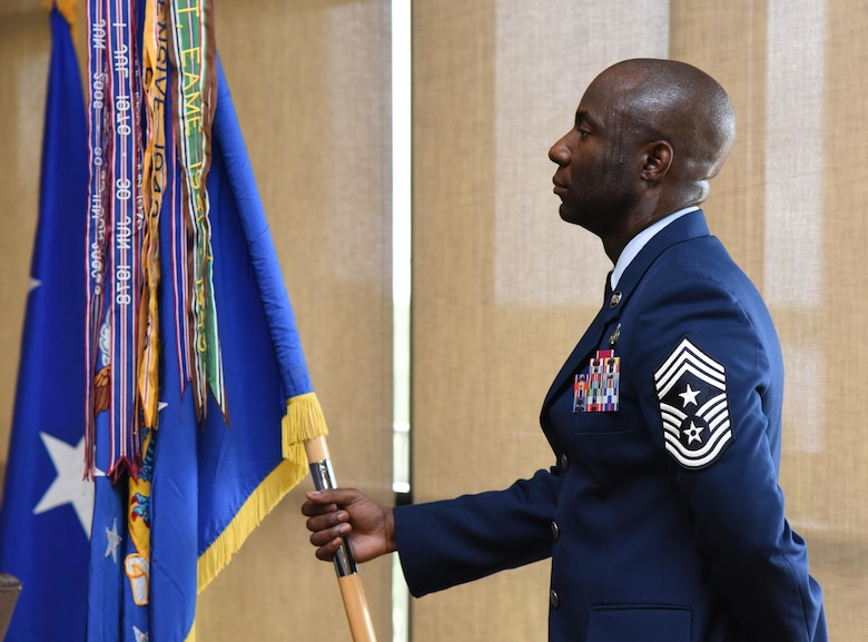 Chief Master Sgt. Vegas Clark, 81st Training Wing command chief, holds the guidon during a change of command ceremony at the Bay Breeze Event Center June 2, 2017, on Keesler Air Force Base, Miss. The ceremony is a symbol of command being exchanged from one commander to the next by the handing-off of a ceremonial guidon. Col. Debra Lovette took command of the 81st TRW from Col. Michele Edmondson. (U.S. Air Force photo by Kemberly Groue)