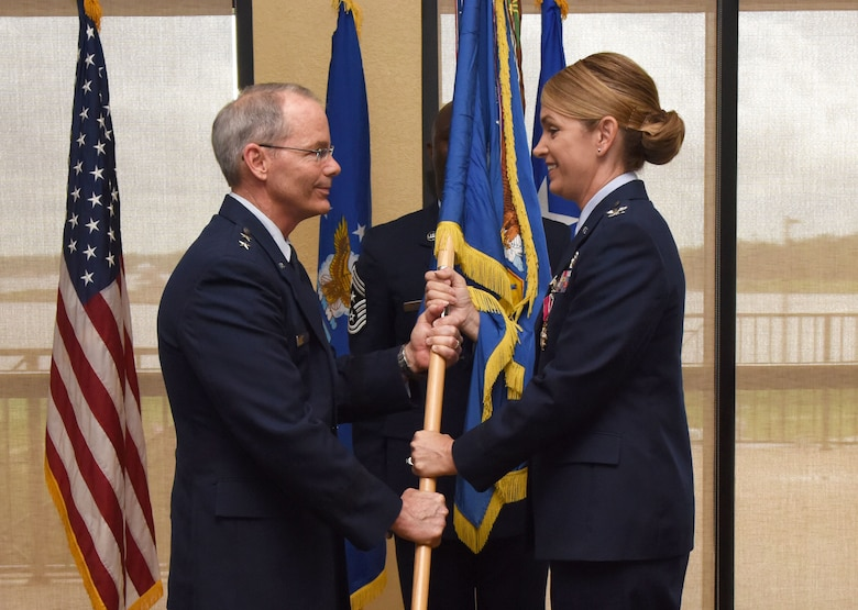 Maj. Gen. Bob LaBrutta, 2nd Air Force commander, takes the guidon from Col. Michele Edmondson, outgoing 81st Training Wing commander, during a change of command ceremony at the Bay Breeze Event Center June 2, 2017, on Keesler Air Force Base, Miss. The ceremony is a symbol of command being exchanged from one commander to the next. Edmondson is now assigned to be the executive officer to the vice chief of staff of the Air Force at the Pentagon in Washington D.C. (U.S. Air Force photo by Kemberly Groue)