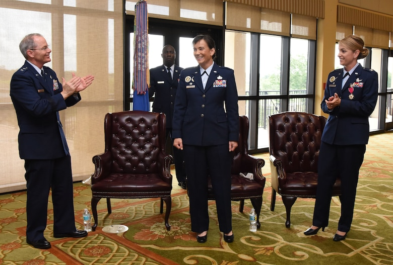 Maj. Gen. Bob LaBrutta, 2nd Air Force commander, and Col. Michele Edmondson, outgoing 81st Training Wing commander, applaud for Col. Debra Lovette, 81st TRW commander, as she assumed command during a change of command ceremony at the Bay Breeze Event Center June 2, 2017, on Keesler Air Force Base, Miss. The ceremony is a symbol of command being exchanged from one commander to the next by the handing-off of a ceremonial guidon. (U.S. Air Force photo by Kemberly Groue)