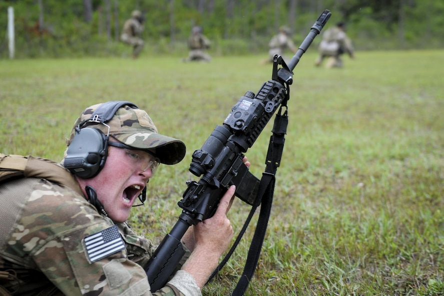 Senior Airman Ethan Pierce, a Deployed Aircraft Ground Response Element member with the 1st Special Operations Security Forces Squadron, commands his team to move during a shoot, move, communicate drill at Hurlburt Field, Fla., June 1, 2017. Shoot, move, communicate is an exercise used to train Defenders to give suppressive fire – fire that hinders an enemy from completing their mission – while under fire, avoid freezing up while in a gun fight, and continue communication with team mates.. (U.S. Air Force photo by Airman 1st Class Dennis Spain)