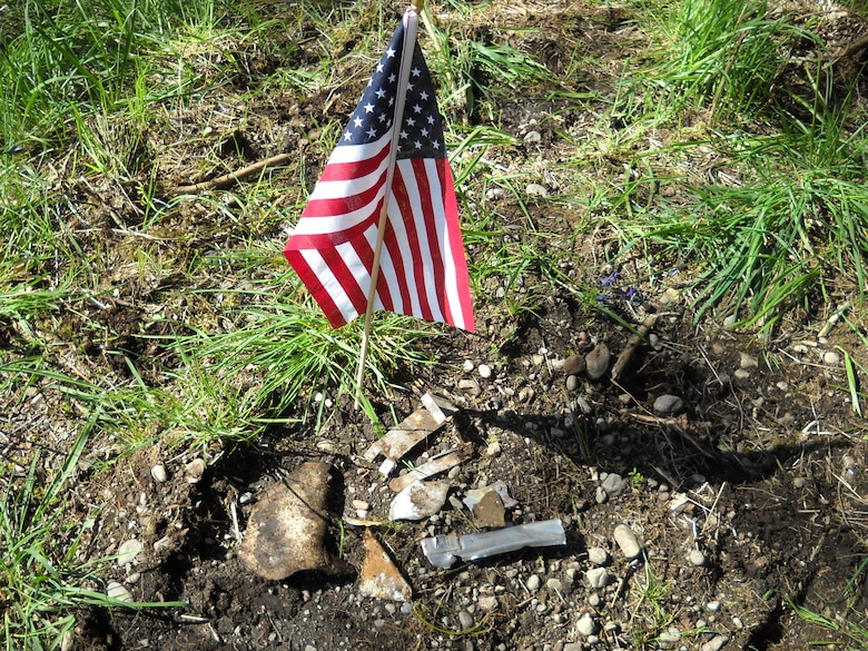 A small U.S. flag is displayed May 5, 2017, beside what is believed to be the remnants of a crashed Convair F-106A Delta Dart jet fighter near its believed crash site at Joint Base Lewis-McChord, Wash. The F-106 was piloted by Capt. Mark Van Stone, 318th Fighter Interceptor Squadron pilot, when it crashed June 24, 1980, on approach to McChord Field. (Courtesy photo)