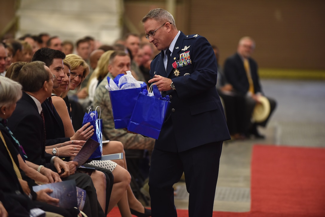Col. J. Christopher Moss, 30th Space Wing commander, presents his family with gifts during his retirement ceremony, June 2, 2017, Vandenberg Air Force Base, Calif. Moss served 26 years in the Air Force, including his last two as commander of the 30th SW. (U.S. Air Force photo by Senior Airman Robert J. Volio/Released)