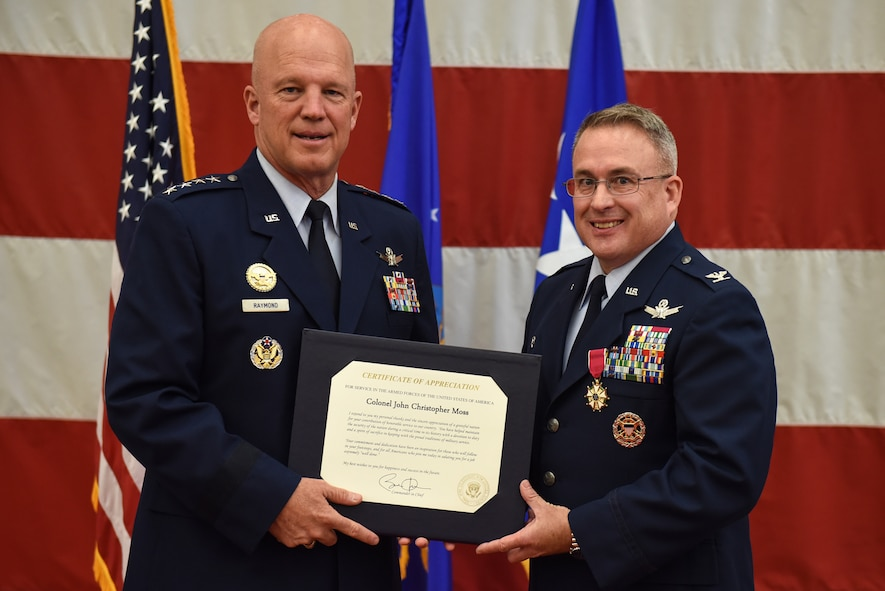 "Gen. John W. ""Jay"" Raymond, commander, Air Force Space Command, presents Col. J. Christopher Moss, 30th Space Wing commander, with a certificate of appreciation during Moss' retirement ceremony, June 2, 2017, Vandenberg Air Force Base, Calif. Moss served 26 years in the Air Force, including his last two as commander of the 30th SW. (U.S. Air Force photo by Senior Airman Robert J. Volio/Released)"