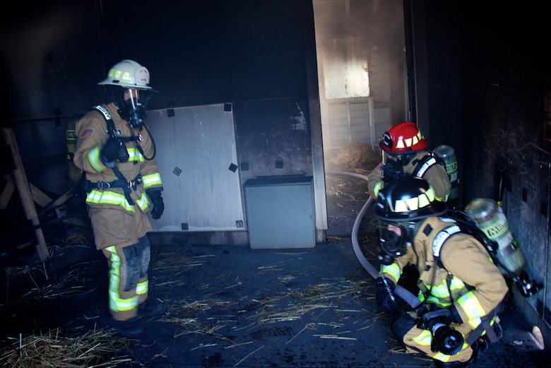 932nd Airlift Wing firefighters trained on intense core special skills particular to their unique jobs on May 21, 2017, at Scott Air Force Base, Illinois.   In preparation, several firefighters lit pallets on fire (in background) to heat up the room, while others began searching for a simulated patient.  These 932nd Civil Engineering Squadron members had already checked the hose system to ensure proper water pressure and availability of the resource in case it was needed to help put out a fire.  Approximately 32 members of the 932nd Civil Engineering Squadron suited up with oxygen tanks to take their turns and get the hot, dark, challenging experience. (U.S. Air Force photo by Lt. Col. Stan Paregien)