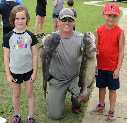 "Trophy winner Joseph Paul (right) catches one of Covella Ponds' ""monster"" fish at Marine Corps Logistics Base Albany's annual Buddy Fishing Tournament, June 3. Joseph's 10.5 pound catfish, earned him two trophies—one for the largest fish in his age category, and a second trophy for overall largest fish of the day. The event, which is held at the installation's Covella Pond, is opened to the communities' youngest anglers and their fishing buddies."