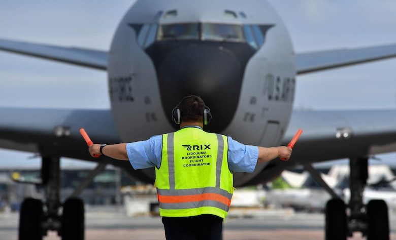 A Riga International Airport personnel marshals a Michigan Air National Guard KC-135 Stratotanker into its parking spot at Riga International Airport, Latvia, June 4, 2017. Two KC-135s flying out of Selfridge Air National Guard Base, Mich., landed at the airport to participate in Saber Strike 2017. (U.S Air Force photo by Senior Airman Tryphena Mayhugh)
