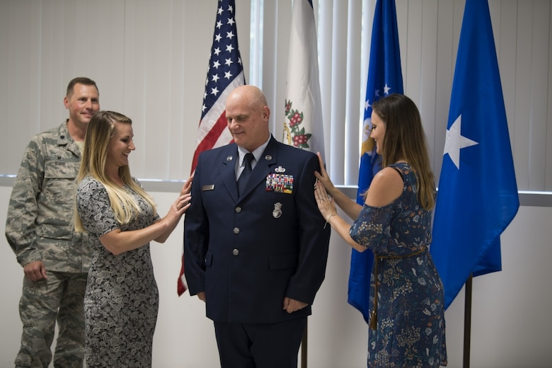 Chief Master Sgt. P. Wayne Hughes stands as his daughters affix his new rank onto his uniform June 3, 2017 during a promotion ceremony held in his honor at McLaughlin Air National Guard Base, Charleston, W.Va. Hughes is a 27-year veteran of Security Forces who will assume the role of chief enlisted manager with this promotion. (U.S. Air National Guard photo by Capt. Holli Nelson)