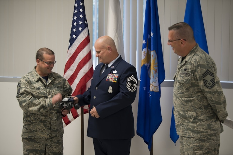 "Chief Master Sgt. John Lowe passes the symbolic ""Jeep Chief"" truck to Chief Master Sgt. P. Wayne Hughes during Hughes' promotion ceremony held June 3, 2017 at McLaughlin Air National Guard Base, Charleston, W.Va. The ""Jeep Chief"" is the newest promoted chief on base and is symbolic of a newly promoted individual in the military. The 130th Airlift Wing Chief's Council presents this token to new Chiefs as a reminder of their role and responsibility in the position. (U.S. Air National photo by Capt. Holli Nelson)"