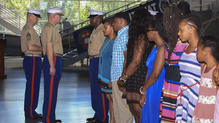 Master Sgt. David Roberts, now officially retired, and his family receive awards and certificates of appreciation from Lt. Col. Charles Winchester, the executive officer of 9th Marine Corps District, aboard Naval Station Great Lakes, Ill., June 2. Roberts, a Bronx native, served in various administrative roles during his career and retired after 23 years of honorable service.