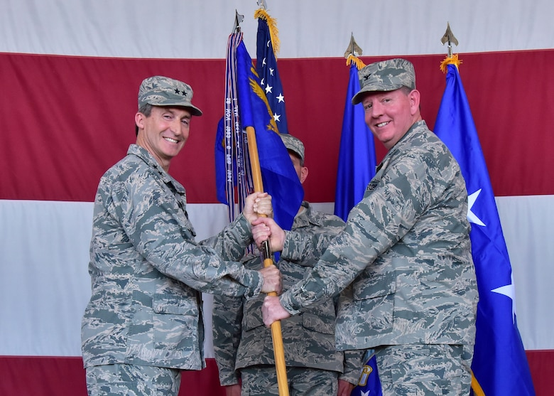 Maj. Gen. Ronald Miller, 10th Air Force commander, hands the 944th Fighter Wing guidon to Col. Bryan Cook Jun 3 during the 944th Fighter Wing Change-of-Command ceremony at Luke Air Force Base, Ariz. (U.S. Air Force photo by Tech. Sgt. Louis Vega Jr.)