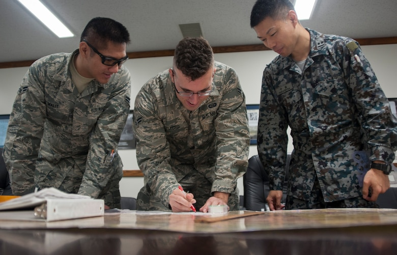 The 35th Operations Support Squadron intelligence analysts and Japan Air Self-Defense Force counterparts plot coordinates on a map in preparation for Red Flag-Alaska 17-2, at Misawa Air Base, Japan, May 26, 2017. RF-A is a field training exercise in a simulated combat environment that ensures the highest level of readiness within the Indo-Asia-Pacific region. (U.S. Air Force photo by Staff Sgt. Melanie A. Hutto)