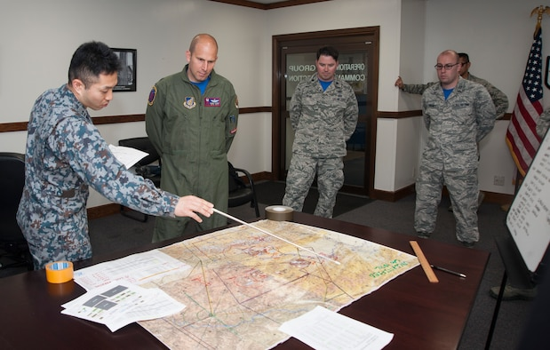 """A Japan Air Self-Defense Force member from Yokota Air Base, Japan, briefs Lt. Col. Kevin Lord, the 35th Operations Support Squadron commander, as part of the mission planning cell at Misawa Air Base, Japan, May 26, 2017. Over the course of a week the 35th OSS intelligence analysts dedicated over 50 hours familiarizing four Japan Air Self-Defense Forces counterparts on mission-set requirements for RED FLAG-Alaska, 17-2. This exercise is one of several that the U.S. and Japan participate in, ensuring the """"fight tonight"""" mentality is strengthened. (U.S. Air Force photo by Staff Sgt. Melanie A. Hutto)"""