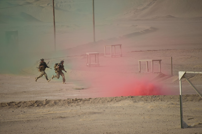 Two Air Force explosive ordnance disposal technicians use smoke grenades for cover as they run across an open area during a joint service EOD field training exercise at an undisclosed location in Southwest Asia, May 25, 2017. EOD teams from each of the four service branches, deployed to five different countries across the AOR, gathered for joint service EOD training, which allowed for the exchange of tactics, techniques and procedures between service branches. (U.S. Air Force photo/Tech. Sgt. Jonathan Hehnly)
