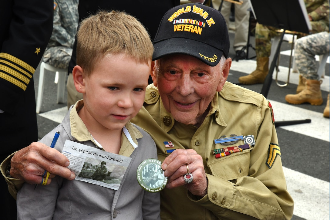 Eugene Kliendl, a World War II veteran, poses for a photo with a French child.