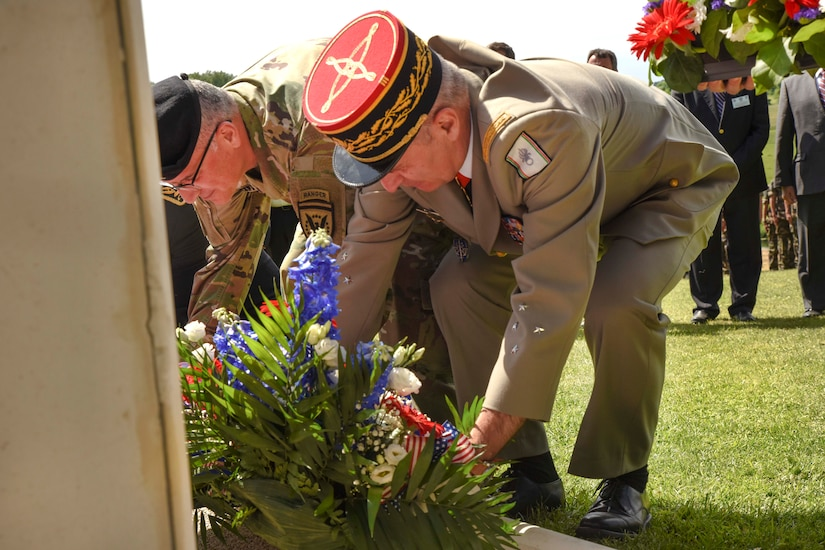 Army Gen. Curtis Scaparrotti, left, commander of U.S. European Command and NATO's supreme allied commander for Europe, and Lt. Gen. Christophe de Saint Chamas, General Officer of Defense and Security Zone West, place a wreath at the foot of the 'Iron Mike' statue in Sainte-Mere-Eglise, France, June 4, 2017.