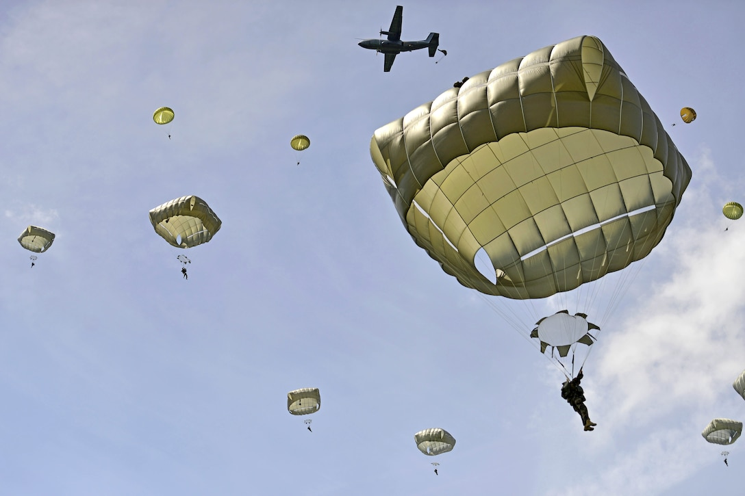 Paratroopers descend to the ground while participating in an airborne operation to commemorate D-Day in Sainte-Mere-Eglise, France
