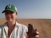 U.S. Army Corps of Engineers Archaeologists Amy Williams displays one of the Acheulean hand axes found in the Nigerien desert that can be dated to more than 1 million years ago. Three hand axes were discovered during a cultural survey of an international air base under construction.