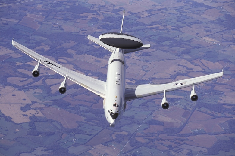 Overall view of a 552nd Air Control Wing E-3C Airborne Warning & Control System (AWACS) aircraft shown over the central United States as it approaches a KC-135R Stratotanker to refuel.  The AWACS aircraft has a large rotating radar mounted above the aircrafts' fuselage and large sensors mounted along the sides of the forward fuselage and below the nose. The E-3C is based at Tinker Air Force Base, Oklahoma. Copyright 2003 Greg L. Davis, Aviation Photojournalist