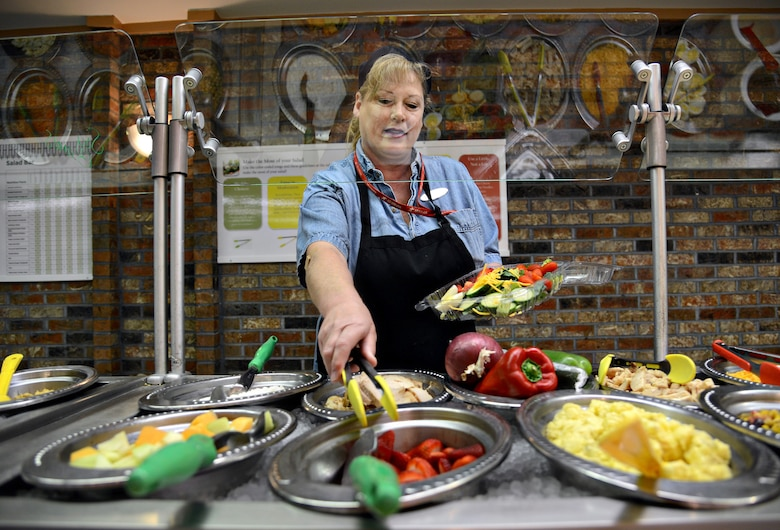 "Karen Dubbe, a cashier at Cafe 3001, assembles a colorful salad for her lunch. The tongs for each food item on the salad bar have either a green, yellow or red handle, based off the ""Look for the Leaf"" concept for nutrition awareness, allowing the customers to be knowledgeable about healthy food selections."